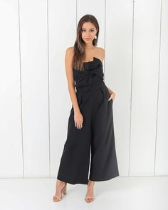 Our Twisted Tales Pocketed Jumpsuit is adorable in this black jumpsuit silhouette that's strapless with a front knot and culotte pant. So flattering with a fitt