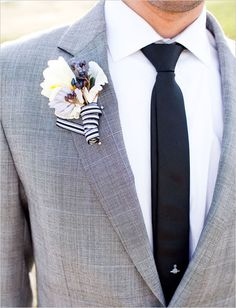 Grey suit with black or navy tie and striped boutonnière..