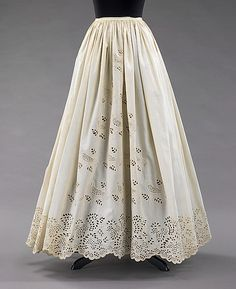 This petticoat features whimsical eyelet embroidery with birds, the form of which is inspired by folk embroidery, and fruit on the vine. A well-loved form of decoration on nineteenth century clothing, eyelet embroidery is a time-consuming process which involves cutting holes out of the fabric to form the desired motif, then meticulously stitching around the hole to complete the design.