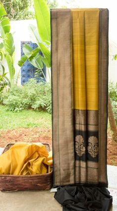 This mustard yellow sari has a lovely texture of Benares tussar. The border and pallu are in black with intricate gold zari work adding elegance to the sari