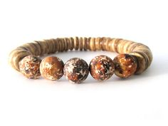 A rugged men's bracelet with 10mm rustic agate beads, 10mm coconut heishi beads (very lightweight!) and antiqued brass accent beads. A rustic and earthy men's beaded stretch bracelet that will look quite handsome on any guy's wrist. Wear alone or stack with your favorite leather wrap, watch or other Rock & Hardware bracelets. Makes a great gift as well!