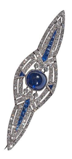 An Art Deco French Sapphire Diamond Gold Brooch. Of geometric outline, the oval cabochon principal sapphire stone bordered by diamond clusters, radiating two lines of calibré-cut sapphires to the sides and single triangular sapphires at the top and bottom, millegrain set. Mounted in platinum. French marks.