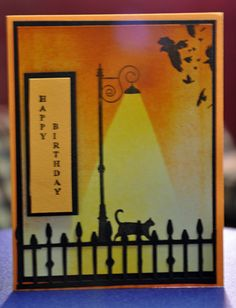 Cat under the lamp stamp by memory box. brayered card with yellows and oranges masking off a triangle area after the first layer of yellow was done. after brayering added the lamppost. then the birds in the corner another memory box stamp, added the words by scarlet empress and the fence is a large punch not sure who makes it but it also had some bats in the posts and I cut those out. - bjl