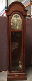RIDGEWAY 84 INCH TALL MOON PHASE CURIO GRANDFATHER CLOCK WITH BRASS FACE. SERIAL NUMBER 89015808. IT HAS BEVELED GLASS FRONT AND SIDES AND A CUSTOM BRASS TAG ON THE BASE INDICATES THAT IT WAS GIFTED IN 1989. MEASURES 22 INCHES WIDE BY 12 INCHES DEEP.