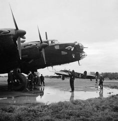 A Handley Page Halifax B Mark II Series I of No. 35 Squadron RAF, being prepared for an engine start in a dispersal, while another aircraft taxies past, at RAF Linton-on-Ouse, Yorkshire.