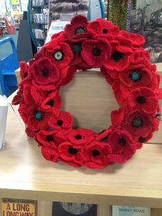Knitted poppy wreath made by Bedford library knit and natter group being used as part of a WW1 display