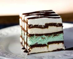 Here's a little something I made for Todd this weekend. It's a frozen grasshopper pie layered between two rows of ice cream sandwiches and coated in sweetened whipped cream. Unlike the last ice cream sandwich cake, this one is made in a square pan an