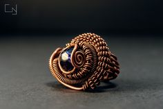 CNJoalharia Wire wrapped ring in copper with a purple plastic bead.