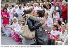Two women kiss in front of an anti-gay/lesbian protest
