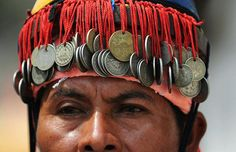 The coin-ornamented headgear of a member of the folkloric group Los Historiantes dances during the Palms and Flowers festival in Panchimalco, south of San Salvador