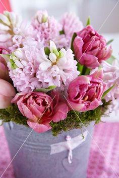 Mooskranz mit Strauss aus rosa Hyazinthen und Tulpen in einem Zinkgefäß – living4media