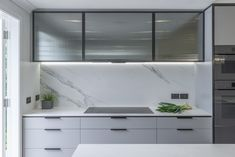 The kitchen is a streamlined galley design with a longer island containing the sink. The overhead cupboard section has fluted, smokey glass inserts with blackened steel frames.  The fluted design element has been repeated on the back of the island panels. The soft lines and colour of the benchtop and splashback contrasts the strong vertical design elements of the framed steel and the vertical fluted glass and island panels.A pantry is hidden behind pocket doors and contains a benchtop… Interior Design Solutions, Vertical Design, Industrial Kitchen Design, Leadlight Windows, Colored Ceiling, Renovations, Kitchen Renovation, Kitchen Design, Slider Door