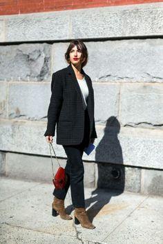 Ga compleet in zwart, met daaronder bruine suede laarzen en een opvallende tas.