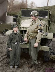 US Staff Sergeant Francis Daggertt of the Military Police of the 11th Armored Division and the German Wehrmacht soldier, the soldier only 10 years old when captured in the German city of Kronach, April 27, 1945    Foto coloreada