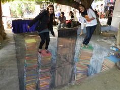 3D chalk pavement art towers of books by Tracy Lee Stum