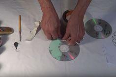 En retirant le papier sur un CD, elle réalise un mandala tout en couleur!