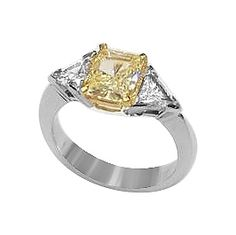 This gracefully modern 3 stone ring features a modern, knife edge setting design in 14K white gold, complimented with a 14K yellow gold center basket; truly a one-of-a-kind design!  The 2 carat canary yellow diamond is accented by 2 .40 carat triangle diamonds, 2.80 ctw. This ring can be set with a combination of gemstones and diamonds, also. Call 212-869-1060 for a price quote.