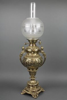 "Lot 151, A handsome Victorian pierced brass oil lamp in the form of a twin handled urn with chimney and etched glass shade, raised on a circular foot, 32""h, est £150-200"