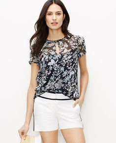 Fresh florals add sheer romance to this light and airy top for an instant pick-me-up. Add a cami beneath for more coverage. Jewel neck. Front keyhole with button closure. Shirred short sleeves. Shirred back yoke.