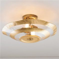 "Metallic Rings Glass Ceiling Lightetallic rings in rich Gold or Silver leaf add sophisticated sparkle to this oversized wavy glass ceiling light. 2x40 watts medium base sockets. 5"" canopy. (9""Hx17.5""W)"