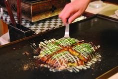 Okonomiyaki - Grilled savory pancake with ingredients like cabbage, noodles, green onion, with brown sauce and mayo (Japan)