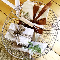 Tone-on-tone wrapping papers are paired with neutral ribbons and embellished with berried sprigs and fern stems.