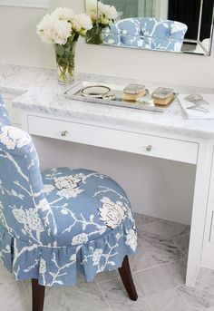 A blue ruffled vanity chair sits on gray marble herringbone floor tiles in front of a white makeup vanity accented with nickel and glass pulls and a Carrera marble countertop fixed under a beveled mirror. White Makeup Vanity, Inside Kitchen Cabinets, Fire Pit Table And Chairs, Leather Recliner Chair, Above Bed, House Of Turquoise, Marble Countertops, White Houses, Family Room