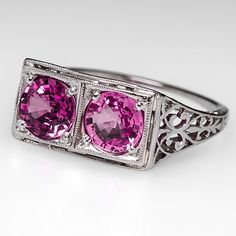 Art Deco 1920's Engagement Ring Twin Pink Sapphires in Platinum. This lovely art deco 1920's engagement ring features twin natural pink sapphires. The ring has ornate milgrain designs and is crafted of solid platinum. It shows some wear from a wedding band but is in good condition overall.