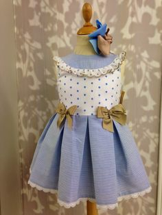 Sweet sleeveless dress blue & white small stripes on skirt & yoke & white with blue diamond dots and tan bows at sides of waist. | ANGELOTTES