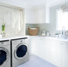 source: Style at Home Kelly Deck - Ethereal laundry room with green glass subway tiles backsplash and white shaker cabinets. Silver front-load washer and dryer, laundry rod, glass canisters holding laundry detergent and West Elm Curved Basket. Instant hot water faucet and crystal chandelier over laundry room sink.