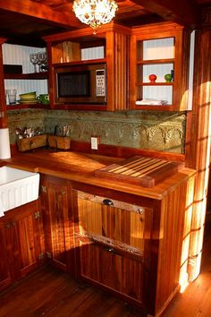 Beautiful stained wood kitchen in tiny home with SS microwave and white porcelain farm sink