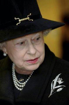 Queen Elizabeth II. She is in black to show respect it highlights her pale complexion. She is wearing her go to strand of pearls.It is a quiet and moment as it was taken at a hospital after the horrific Tsunami in Asia.