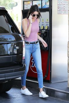 Kendall Jenner wears a striped tank top, belted jeans, white sneakers, and aviator sunglasses