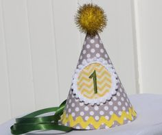 This is a fabric party hat that is made out of fabric and interfacing. It is embellished with coordinating ric rac and topped with a