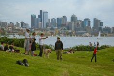 people standing on a hill in gasworks park in seattle with downtown in the distance across the lake