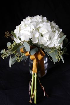 White Hydrangeas bouquet with cascading seeded eucalyptus and a mustard yellow or burnt orange looped ribbon accent