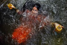 A Hindu devotee takes a holy dip as she collects holy water from the Bagmati river during the Bol Bom pilgrimage outside Katmandu. Devotees walk miles barefooted before offering the water at the Pashupatinath lord Shiva temple in Katmandu. PHOTOGRAPH BY: NIRANJAN SHRESTHA / ASSOCIATED PRESS