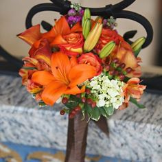 Rachel and Peter. The bridesmaids carried bouquets of lilies, roses, berries, stock, and calla lilies.  Image Credit: Carrie Wildes Photography.