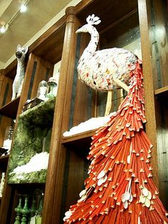 a fabulous paper mache peacock with its tail composed of bright orange chopstick wrappers and plastic spoons