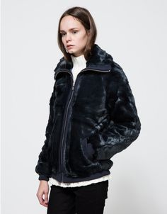 From Ganni, a mid weight faux fur jacket with bomber jacket styling in Total Eclipse.  Features tall collar, full silver zipper, ribbed zipper strip, raglan sleeves, full length sleeve, ribbed cuff, front slanted pockets, ribbed pockets, ribbed cuff and f