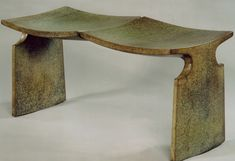 This classic, cast bronze bench has the appearance of two stools fused together to create a sculptural, sloping form.