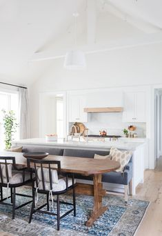 Dining Table/Kitchen Island Combo Home Tour via Amber Interiors and Photos via Tessa Neustadt Kitchen Island Booth, Kitchen Island Dining Table, Kitchen Islands, Dining Tables, Kitchen Island With Bench Seating, Dining Area, Eat In Island Kitchen, Kitchen Cabinets, Kitchen Island And Breakfast Nook
