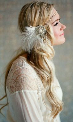 romantique et bohème. La mariée a des cheveux blonds très longs, légèrement ondulés et un peu «wavy», laissés lâches. elle porte très bas un headband majestueux.composé de perles, de bijoux dorés et bleus et bien sûr, d'une grosse plume blanche. La taille du bijou étant conséquente, il est préférable d'avoir les cheveux très longs et assez épais pour ne pas que l'accessoire nous cache trop la tête.