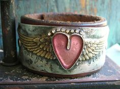 A heart centered between angel wings on a leather cuff bracelet. Soldered jewelry.