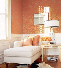 Used above white wainscoting, metallic wallpaper adds a hint of glamour to this sitting room. A white chaise invites guests to recline next to a stack of coffee table books, while a cowhide rug adds an unexpected surprise underfoot. Orange Wallpaper, Metallic Wallpaper, Modern Wallpaper, Wallpaper Designs, Beautiful Wallpaper, Room Colors, Home Decor Inspiration, Decor Ideas, Small Spaces