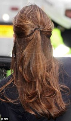 Kate's hair was, sensibly given the gusty conditions, swept back in a ¿half up, half down do¿, showing off a pair of Annoushka pearl earring...