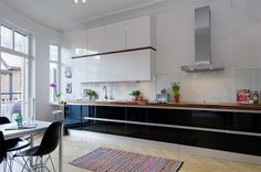 Light and airy high gloss kitchen! Lovely fishbone flooring.