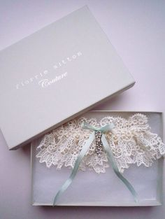 Simple lace garter with a blue ribbon threaded through.