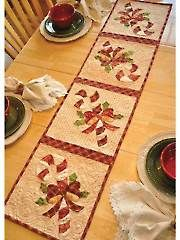 "Vintage Blessings December Table Runner Pattern this vintage-inspired runner that features sweet candy canes wrapped in a tidy bow. You can even use each individual square to make matching place mats! Finished size is approximately 12 1/2"" x 53""."