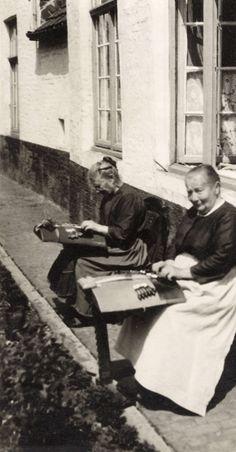 Vrouwenarbeid, kantklossen. Kantklossende vrouwen voor hun huis in Brugge. België, Brugge, 1930.